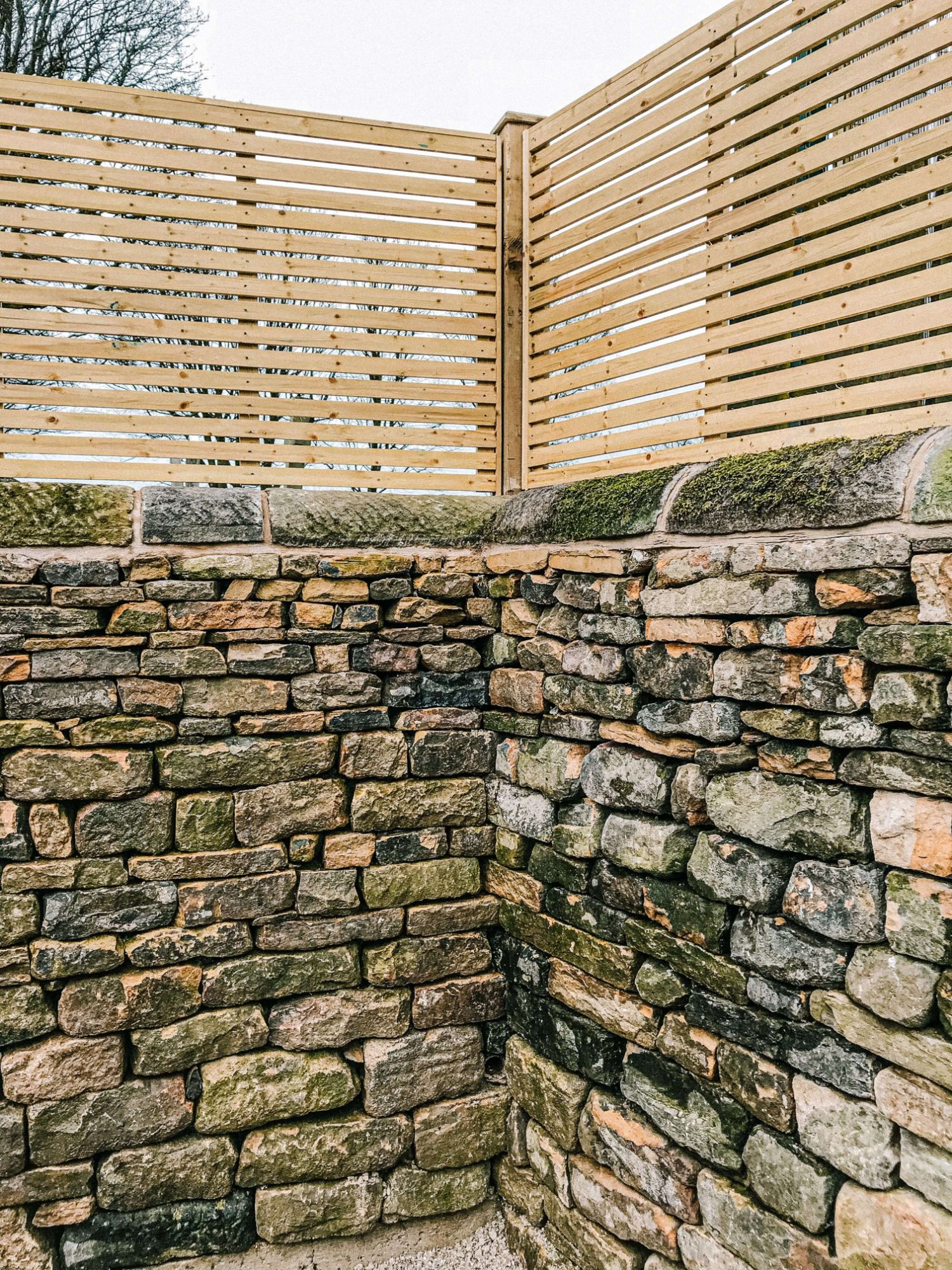 A photo of a corner dry stone wall with a fence above created by the Silver Oak team