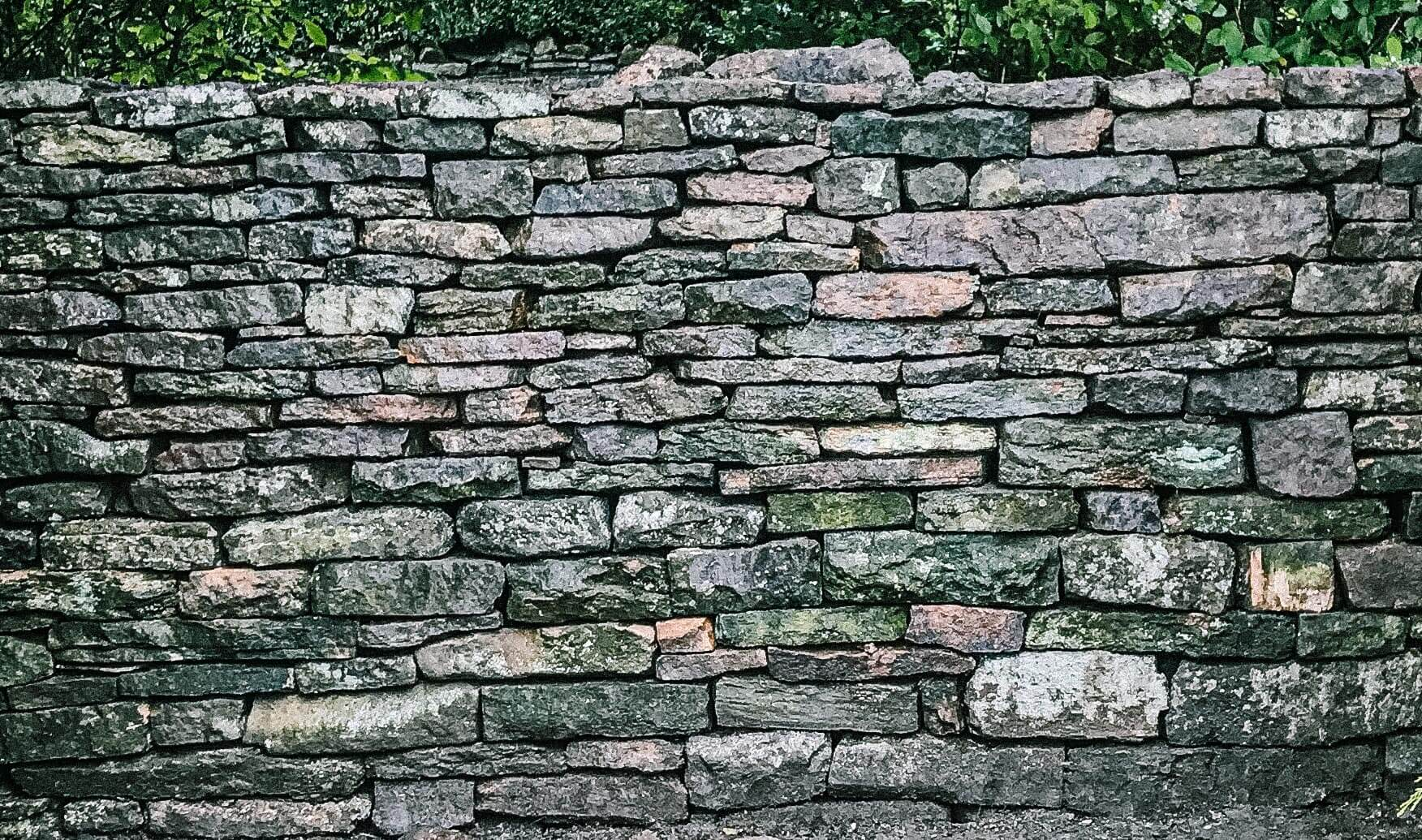 A close up photo of a grit stone dry stone wall in Sheffield
